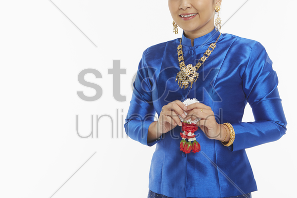 woman in traditional clothing holding on to a flower garland stock photo