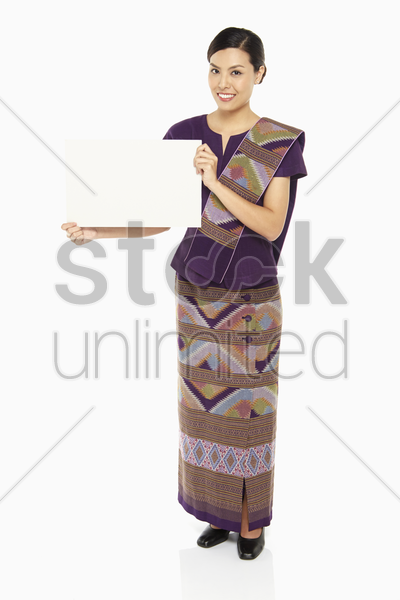 woman in traditional clothing holding up a blank placard stock photo