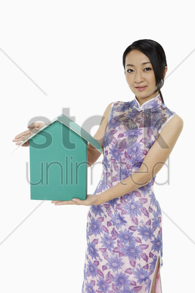 woman in traditional clothing holding up a cardboard house stock photo