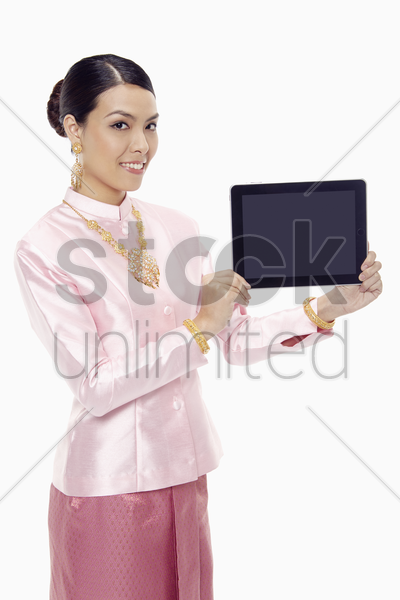 woman in traditional clothing holding up a digital tablet stock photo