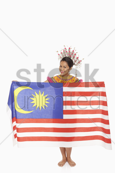 woman in traditional clothing holding up a malaysian flag stock photo