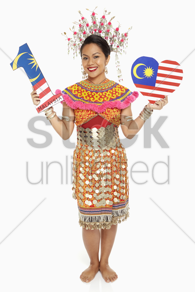 woman in traditional clothing holding up a number one shape and a heart shape stock photo