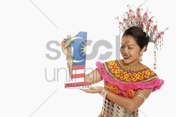 woman in traditional clothing holding up a number one shape stock photo