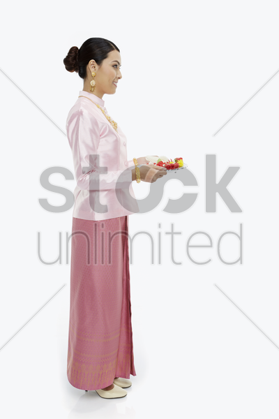 woman in traditional clothing holding up a tray with thai flower garlands stock photo