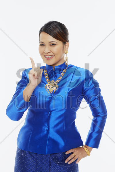 woman in traditional clothing holding up index finger stock photo