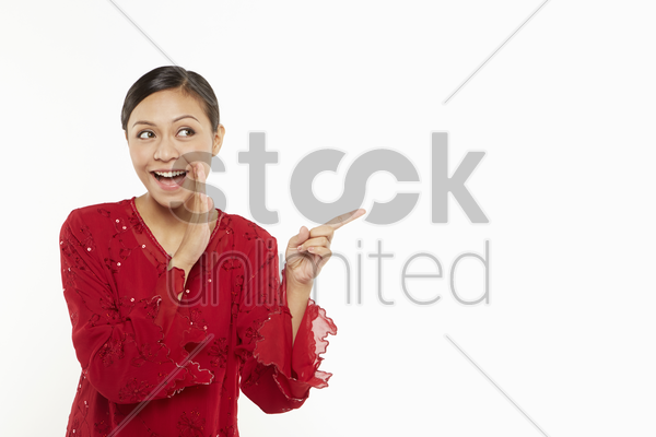 woman in traditional clothing pointing to the left stock photo