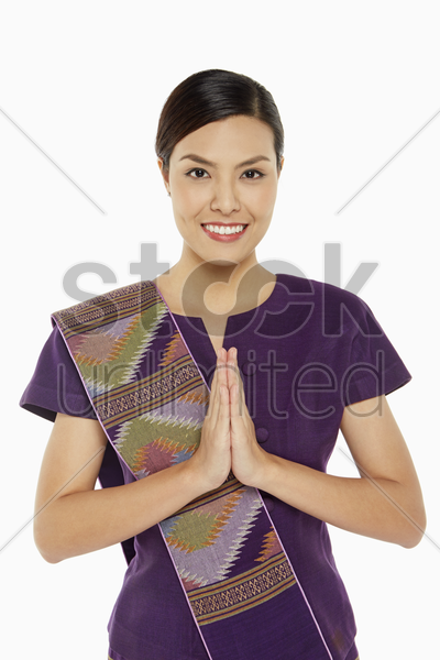 woman in traditional clothing showing greeting gesture stock photo