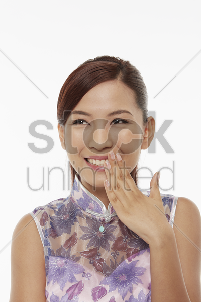woman in traditional clothing showing hand gesture and giggling stock photo