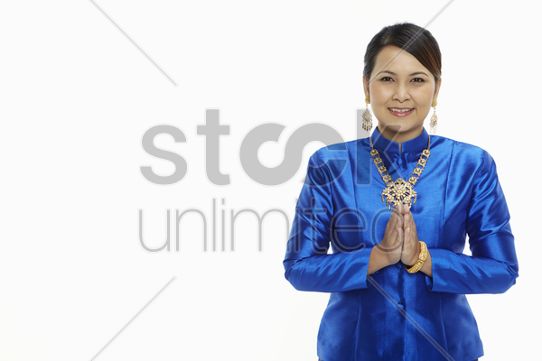 woman in traditional clothing showing hand greeting gesture stock photo