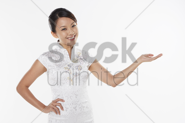 woman in traditional clothing smiling and showing hand gesture stock photo