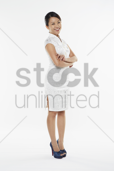 woman in traditional clothing smiling at the camera with arms crossed stock photo