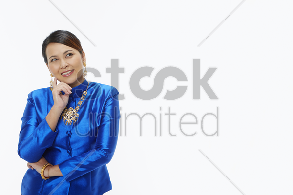 woman in traditional clothing smiling while contemplating stock photo