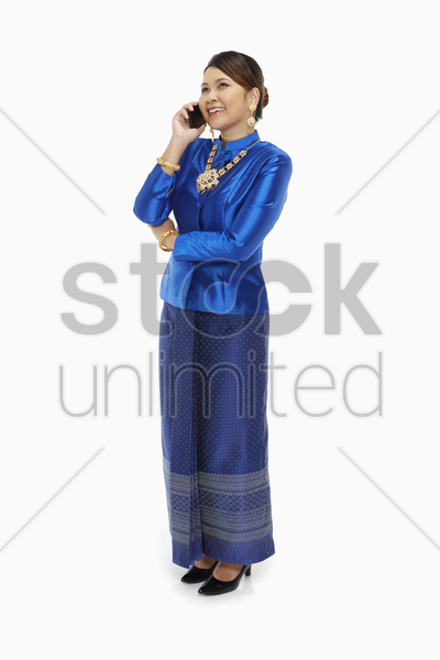 woman in traditional clothing talking on the phone stock photo