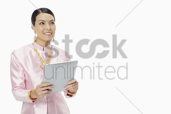 woman in traditional clothing using a digital tablet stock photo