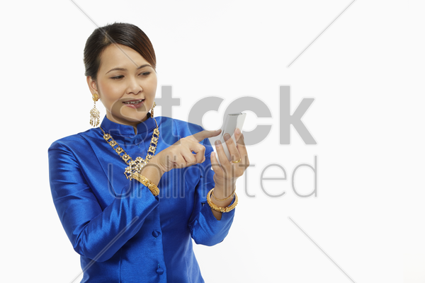 woman in traditional clothing using a mobile phone stock photo