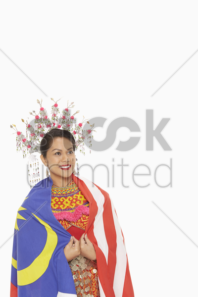 woman in traditional clothing wrapped around with a malaysian flag stock photo
