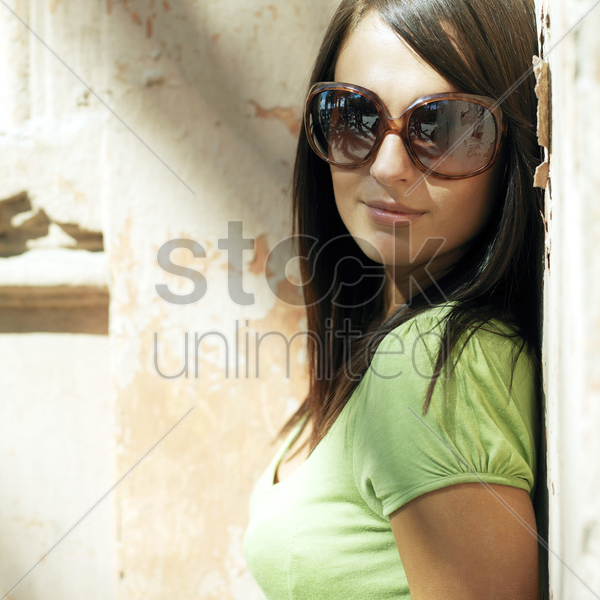woman in trendy sunglasses smiling at the camera stock photo