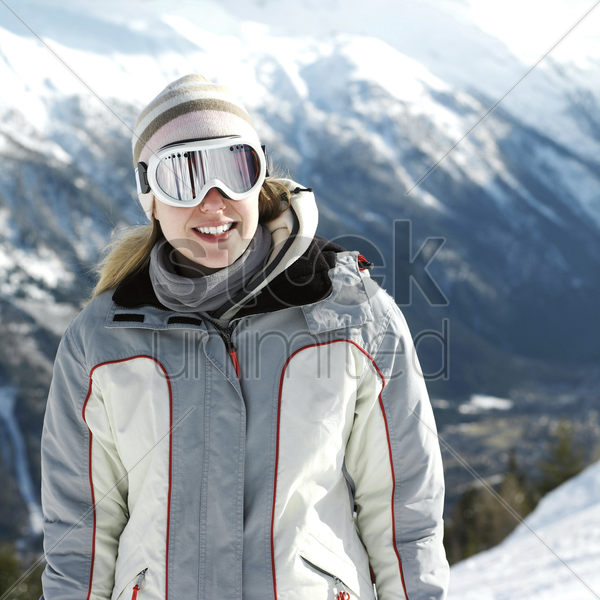 woman in warm clothing and ski goggles smiling stock photo