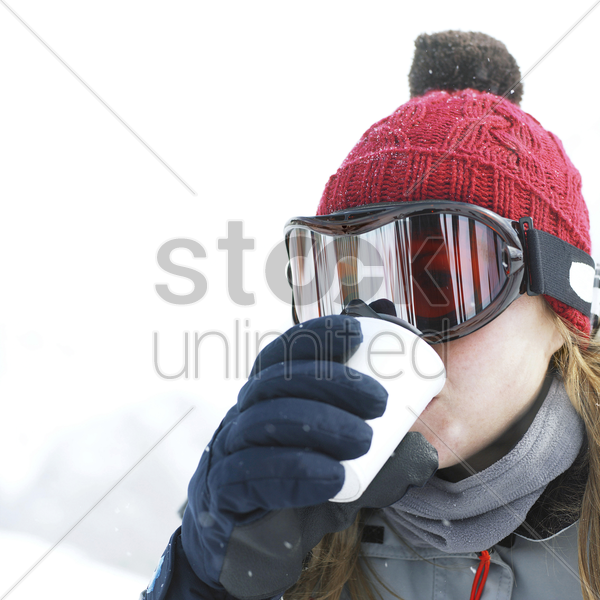 woman in warm clothing enjoying a cup of hot drink stock photo