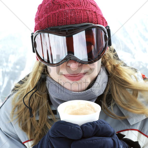 woman in warm clothing holding a cup of hot drink stock photo