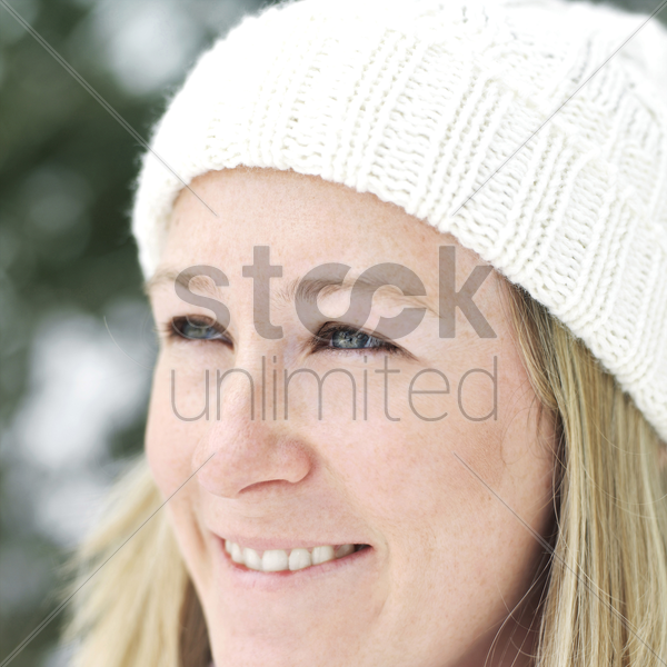 woman in white knitted hat smiling stock photo