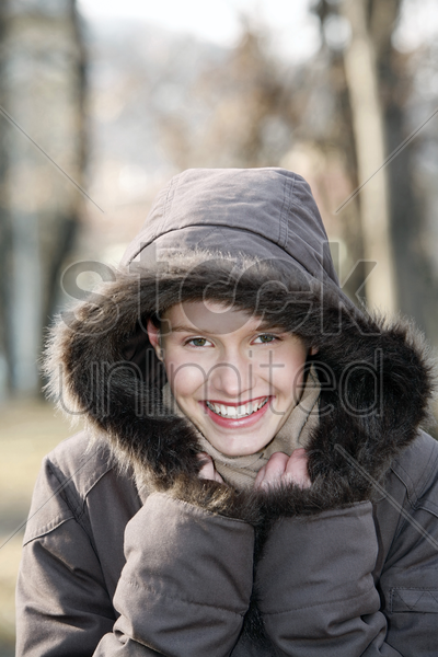 woman in winter clothing smiling at the camera stock photo