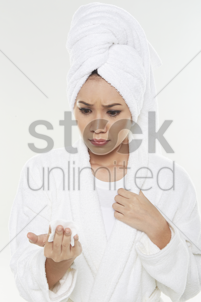 woman inspecting her facial cotton stock photo