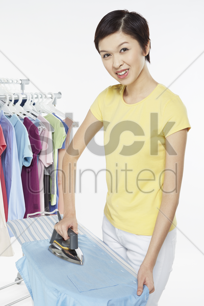 woman ironing clothes stock photo