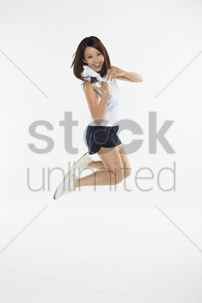 woman jumping in the air while holding water bottle stock photo