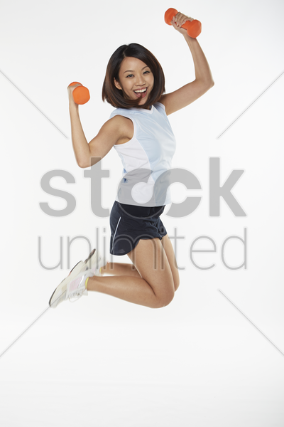 woman jumping in the air while lifting dumbbells stock photo