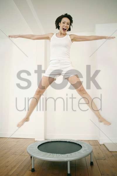 woman jumping on a trampoline stock photo