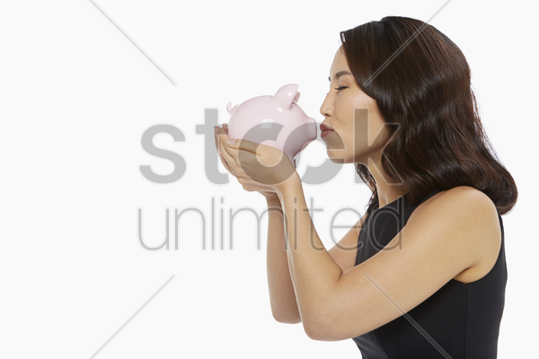 woman kissing a piggy bank stock photo