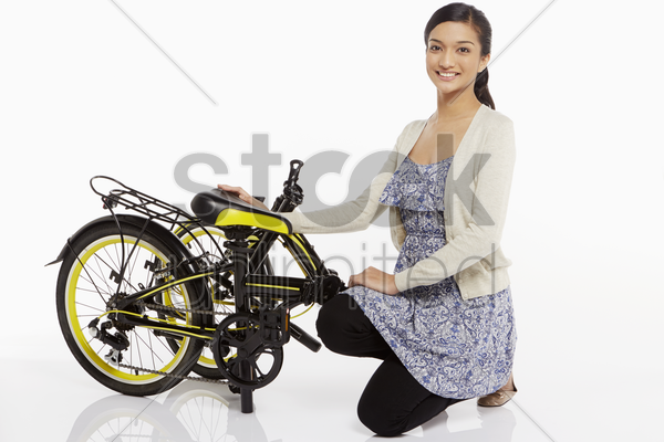 woman kneeling beside a folded bicycle stock photo