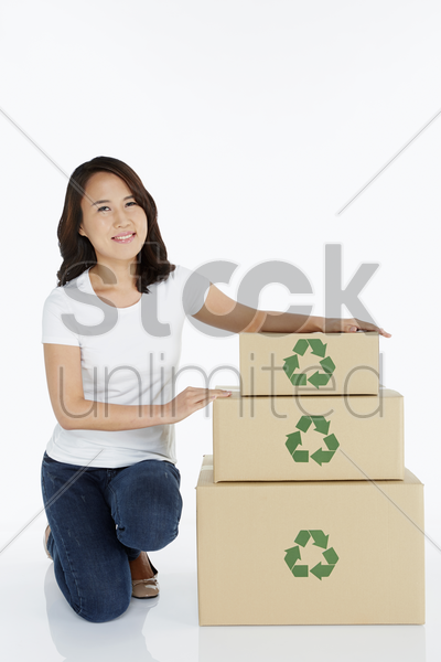 woman kneeling beside a stack of cardboard boxes stock photo
