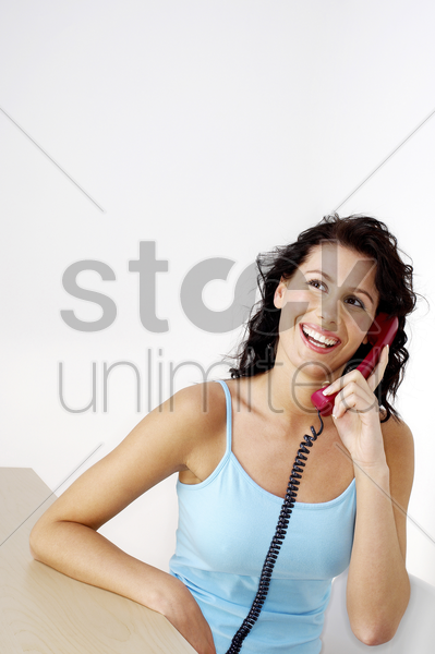woman laughing while talking on the phone stock photo