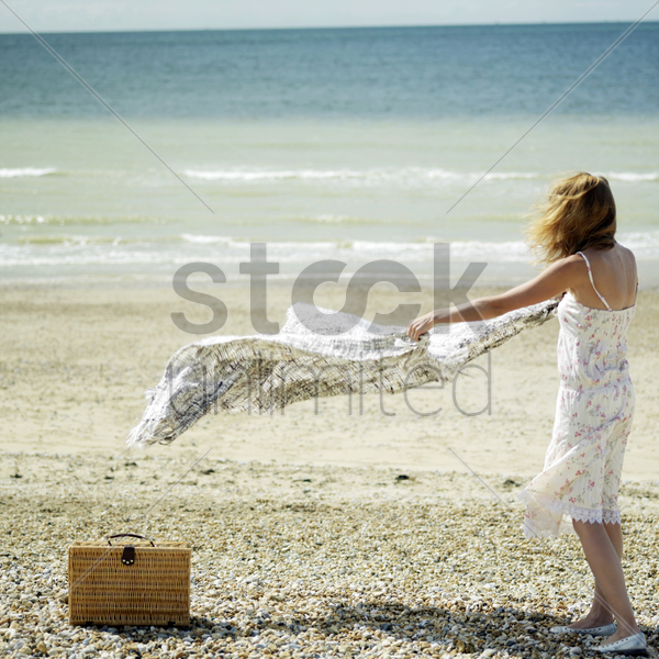 woman laying down picnic blanket on the beach stock photo