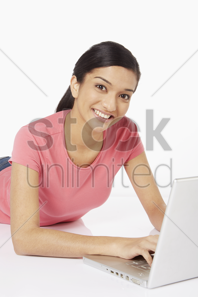 woman laying on the floor, using laptop stock photo