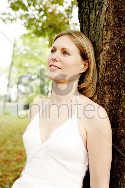 woman leaning a against a tree thinking stock photo