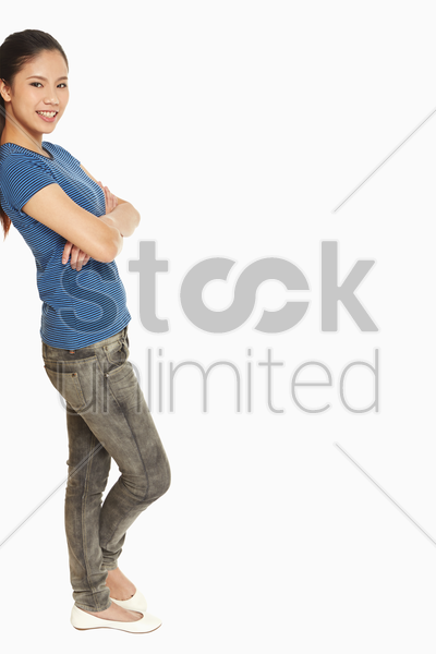 woman leaning against a wall, smiling stock photo