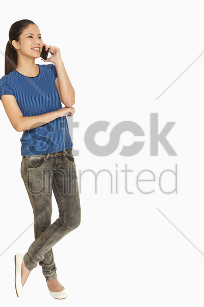 woman leaning against a wall while talking on mobile phone stock photo