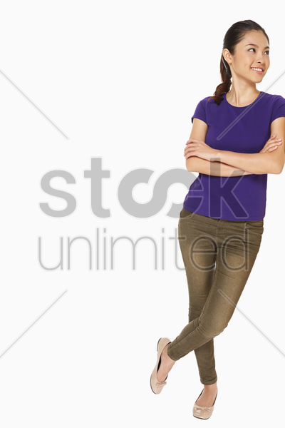 woman leaning against a wall stock photo