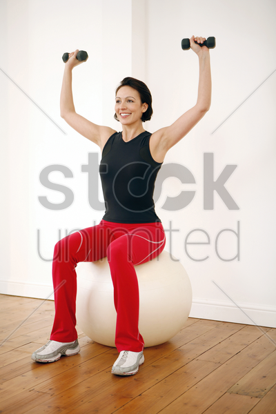 woman lifting dumbbells while sitting on a fitness ball stock photo