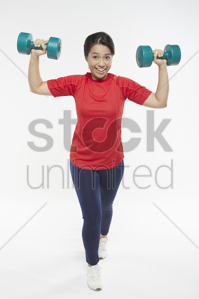 woman lifting dumbbells stock photo