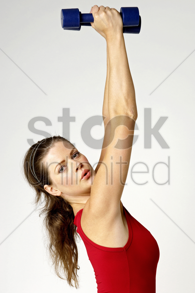 woman lifting up dumbbells stock photo