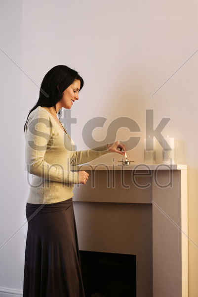 woman lighting up candles stock photo