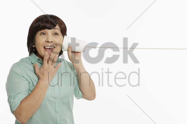 woman listening to a cup phone stock photo