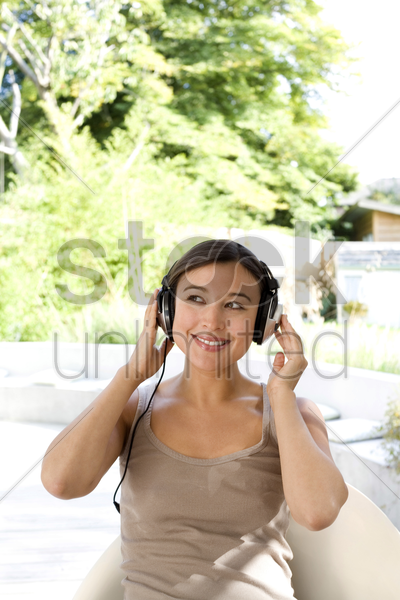 woman listening to music on headphones stock photo