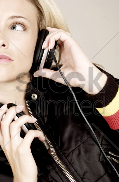 woman listening to music on the headphones stock photo