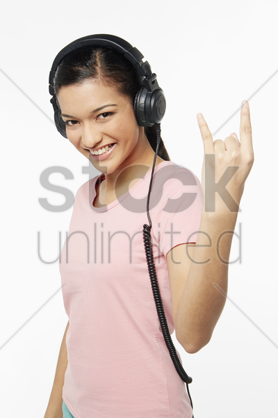 woman listening to music through the headphone stock photo