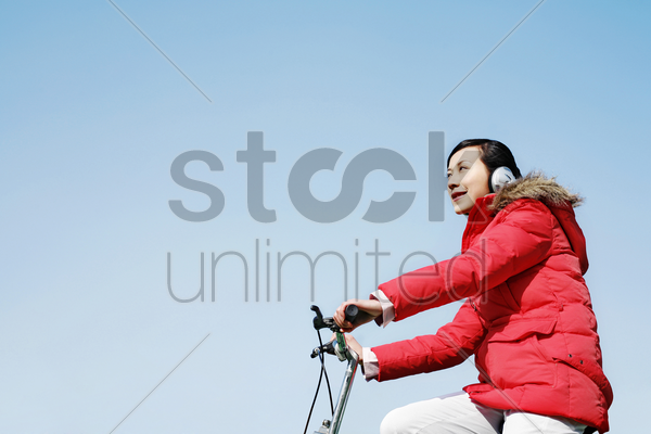 woman listening to music while cycling stock photo
